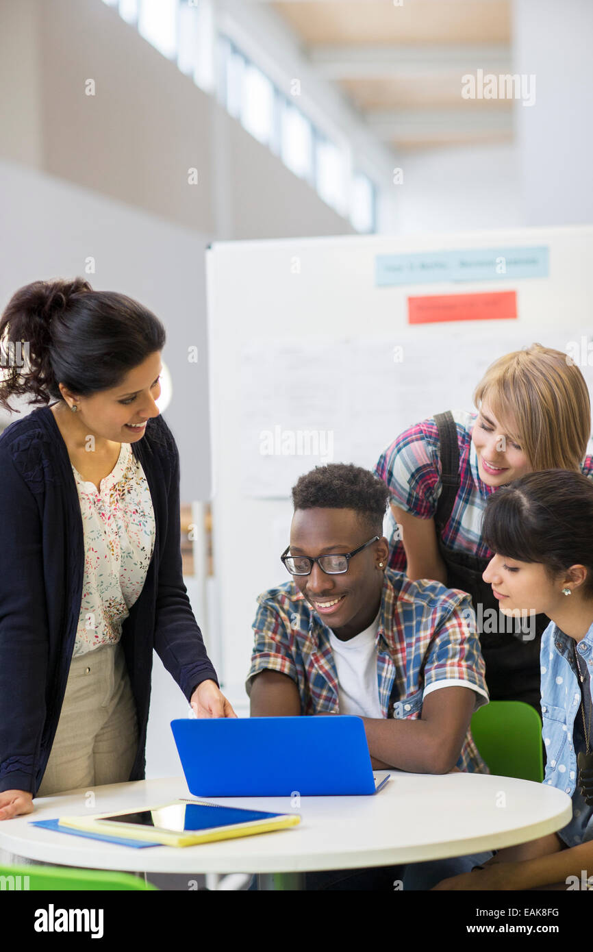 Students and teacher working with laptop - Stock Image