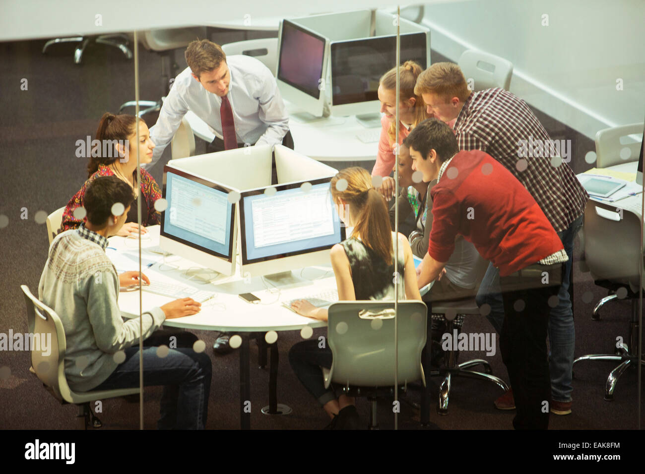 Students during IT lesson in modern classroom with glass walls - Stock Image
