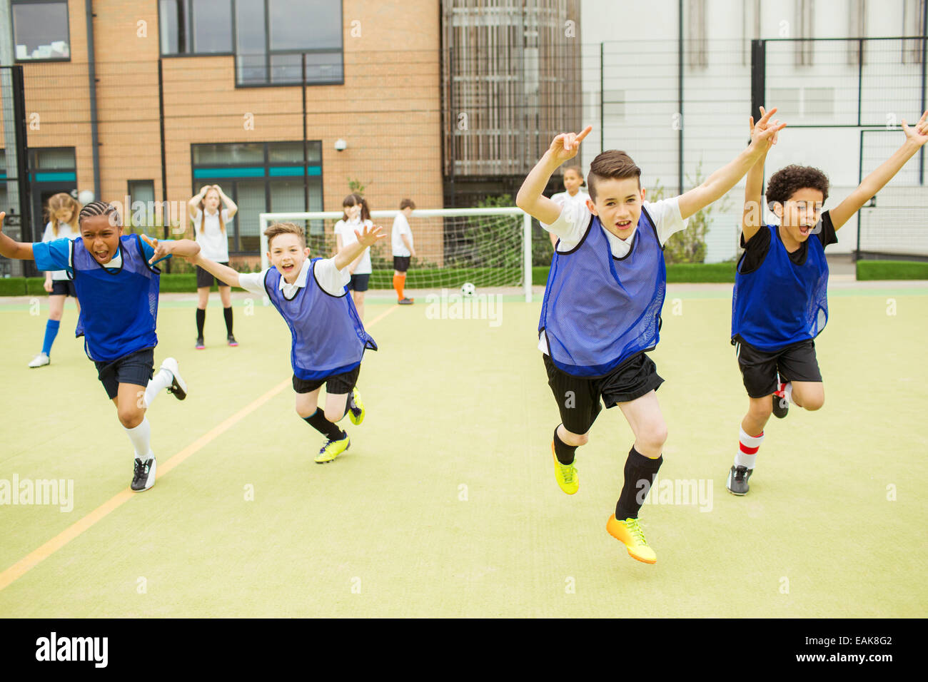 Schoolboys wearing sport uniforms running with arms raised in soccer field in front of school - Stock Image