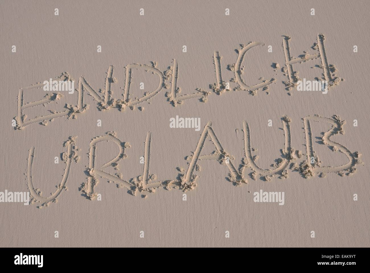 Writing in the sand 'endlich Urlaub', German for 'finally holidays' - Stock Image