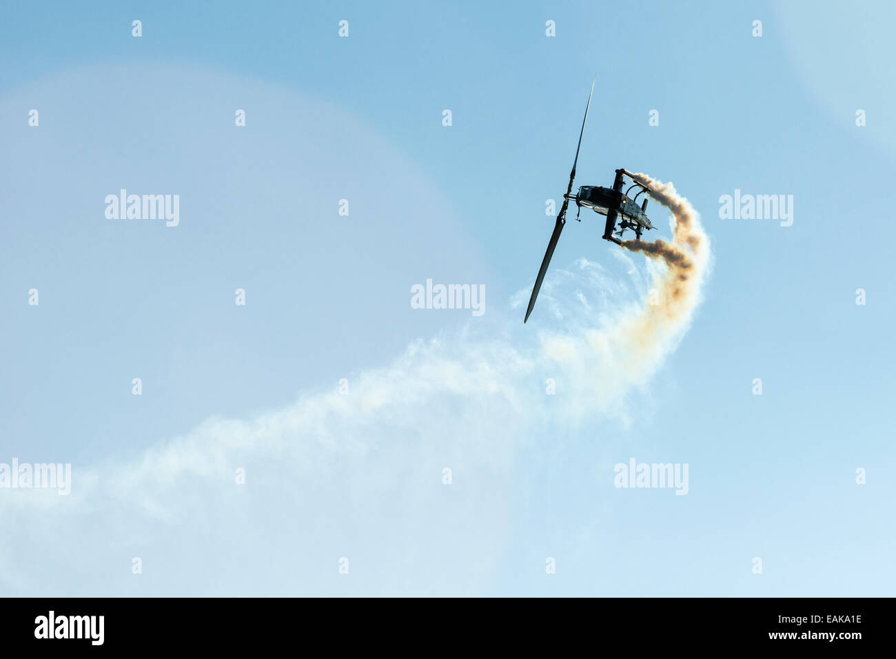 A helicopter, releasing smoke, is performing stunts in the air, Zeltweg, Steiermark, Austria - Stock Image