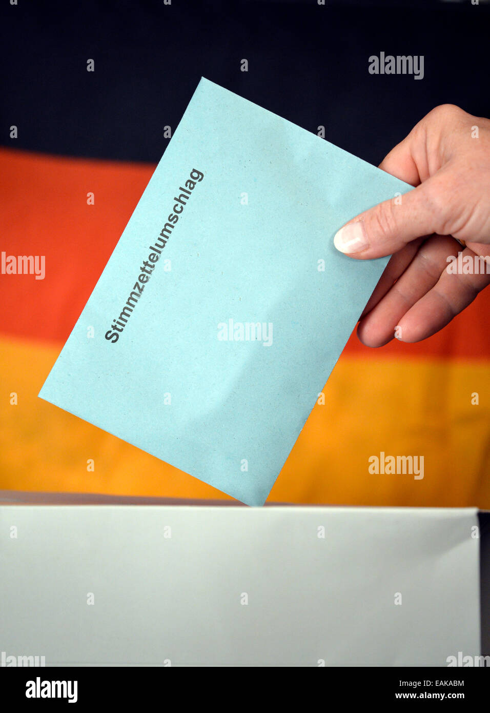 Symbolic image, elections to the Bundestag, hand putting a ballot envelope into a ballot box, in front of the flag - Stock Image