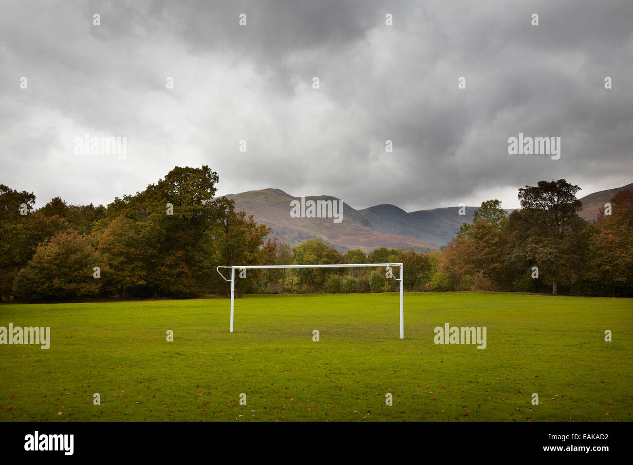 football pitch in autumn with mountains behind and trees, winter football season bad weather, Lake district England - Stock Image