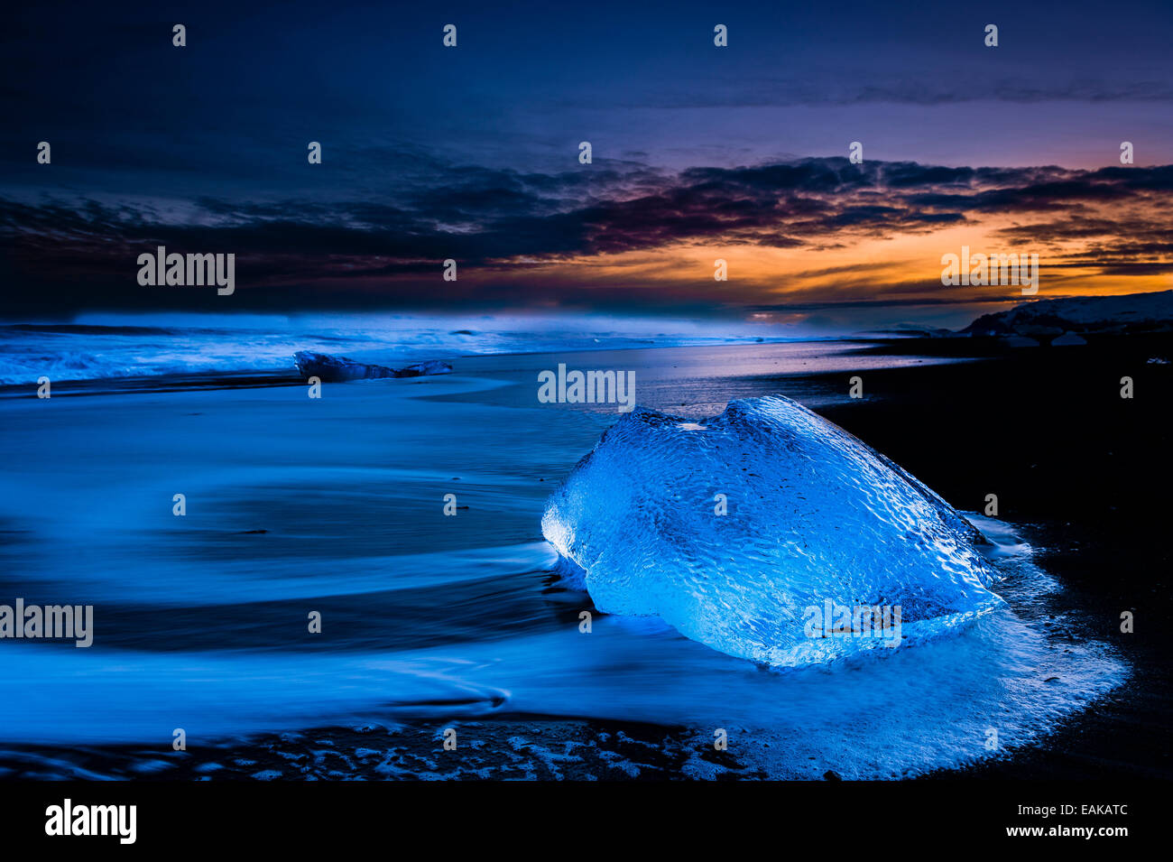 Chunk of ice on black lava sand beach at the blue hour, Jökulsárlón lake, Vik, Iceland - Stock Image