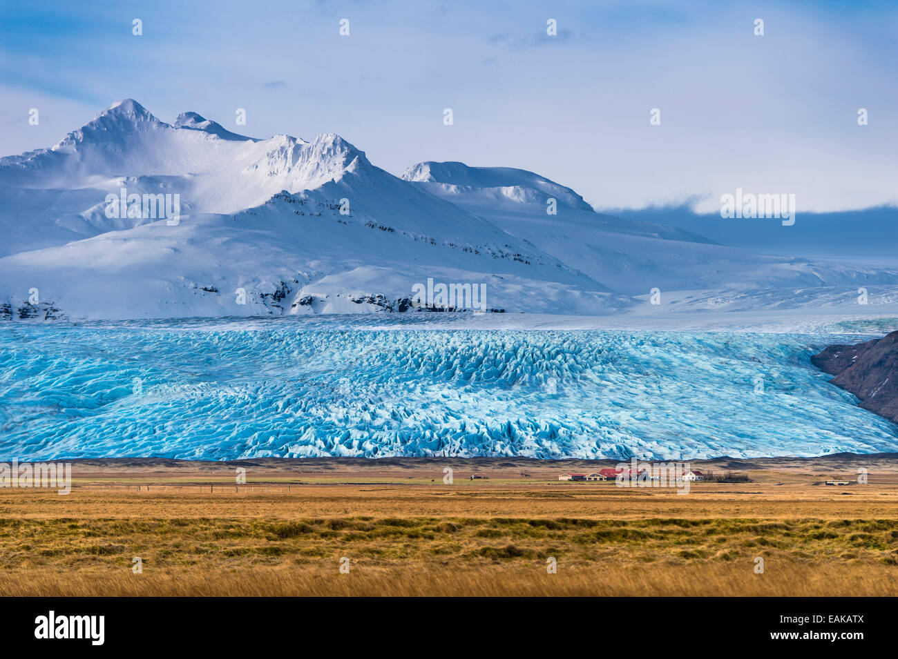 Icelandic farmstead with glacier tongue and snow-covered mountains, Höfn, Iceland Stock Photo