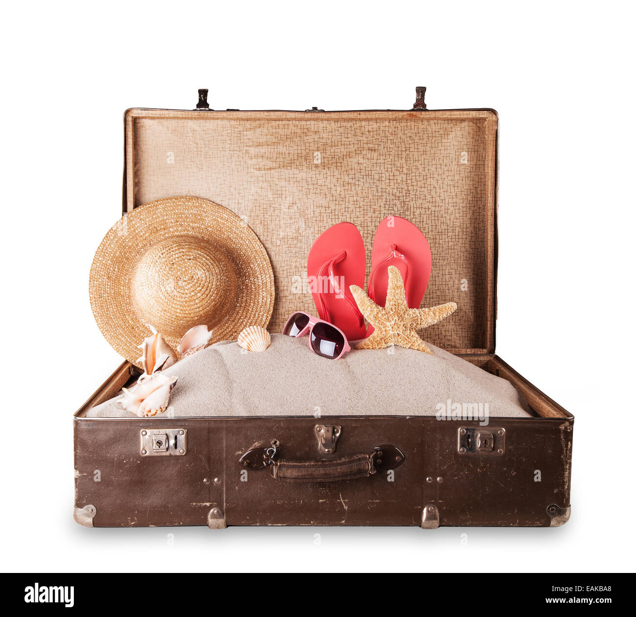 Isolated shot of retro suitcase with accessories on beach - Stock Image