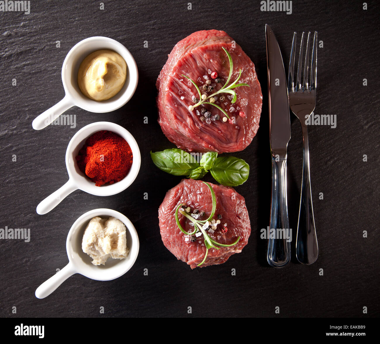 Pieces of red raw meat steaks with herbs, served on black stone surface. Shot from upper view. Stock Photo
