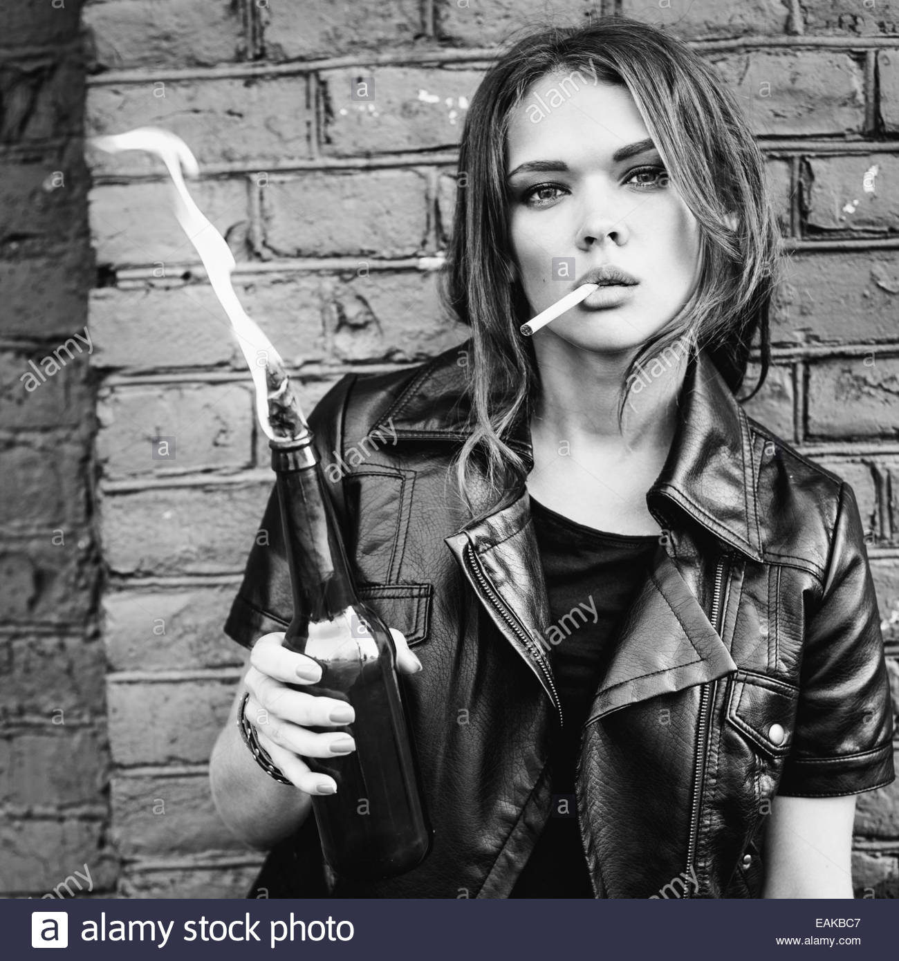 Black and white portrait of a beautiful girl smoking with a molotov