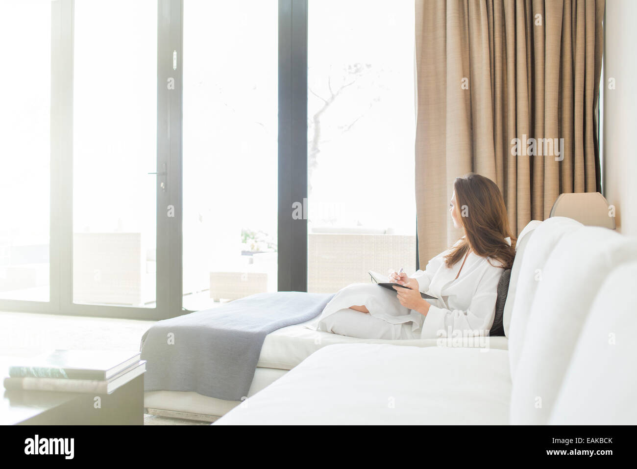 Woman wearing white bathrobe reclining on sofa in living room and looking through window - Stock Image