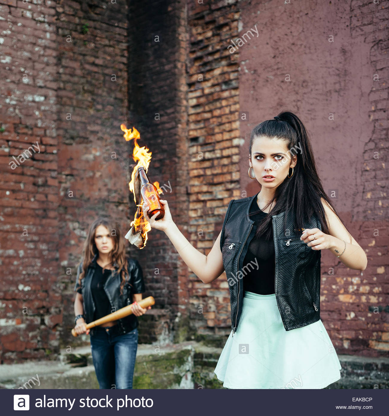 Two Bad girls hooligans with Molotov cocktail bomb in the street.  Outdoor lifestyle portrait - Stock Image