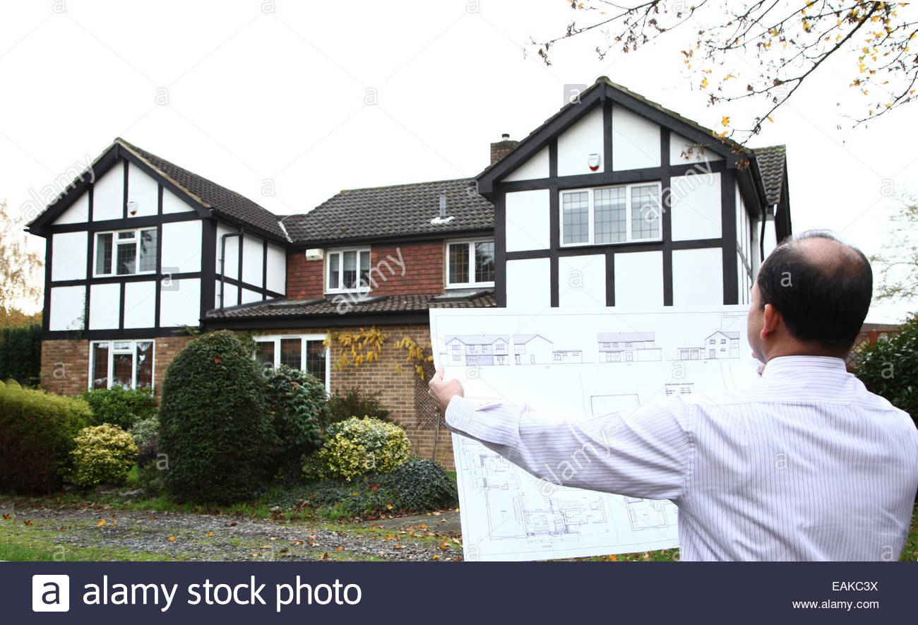 Surveyor or Architect holding plans to a large house - Stock Image