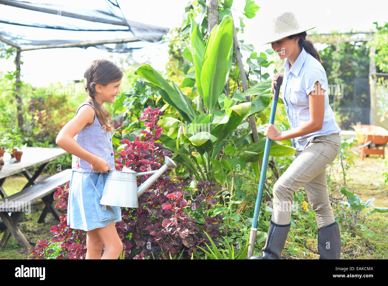 Smiling woman with shovel and girl with watering can working in garden - Stock Image