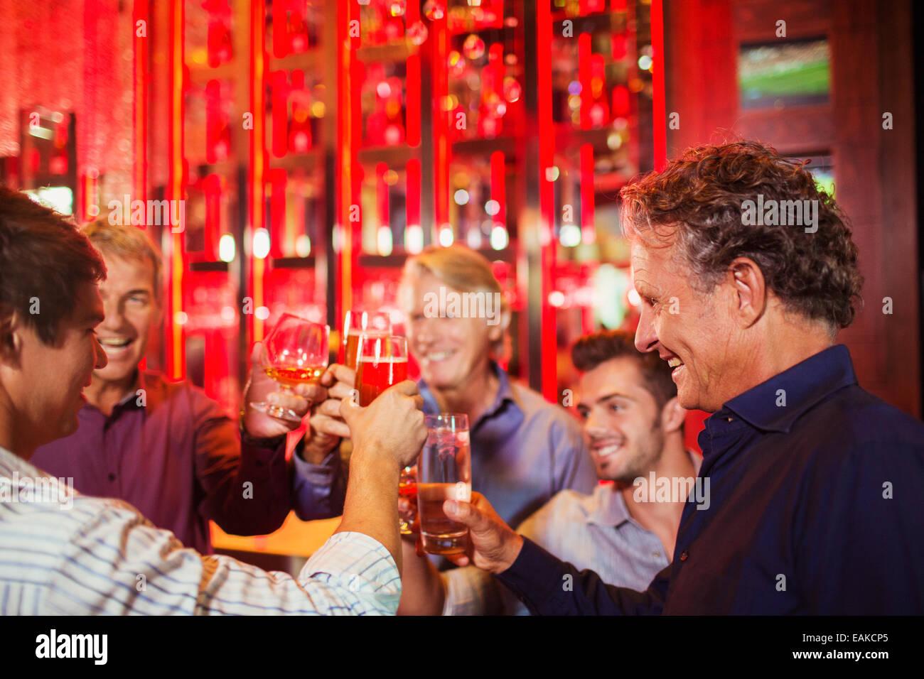 Five smiling men raising toast in bar - Stock Image