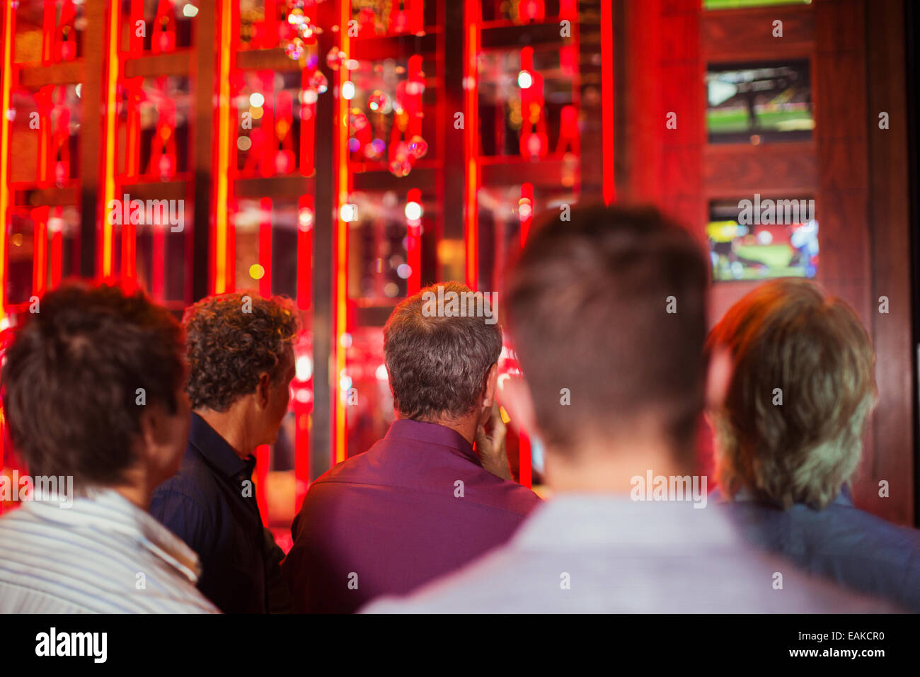 Rear view of group of men watching TV in bar - Stock Image