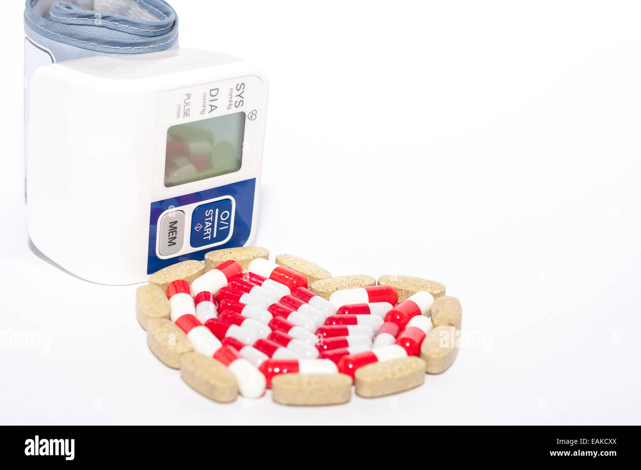 Digital Blood Pressure and heart made of pills on white background - Stock Image