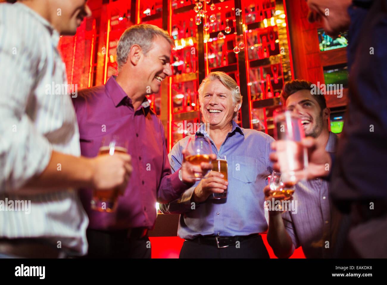 Group of smiling men having drink in bar - Stock Image
