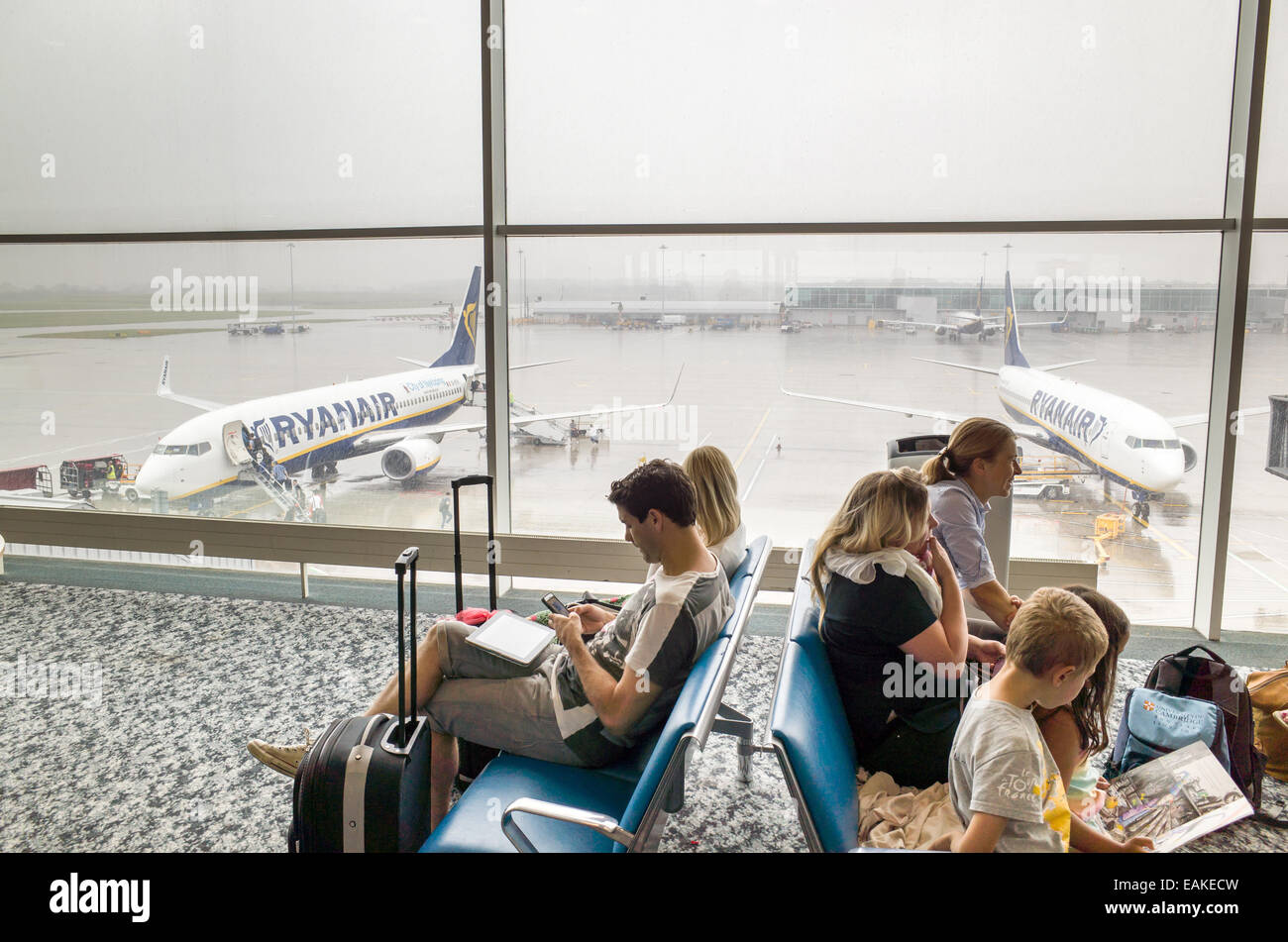 Passengers waiting to board Ryanair plane at Stansted Airport departure gate, England, UK - Stock Image