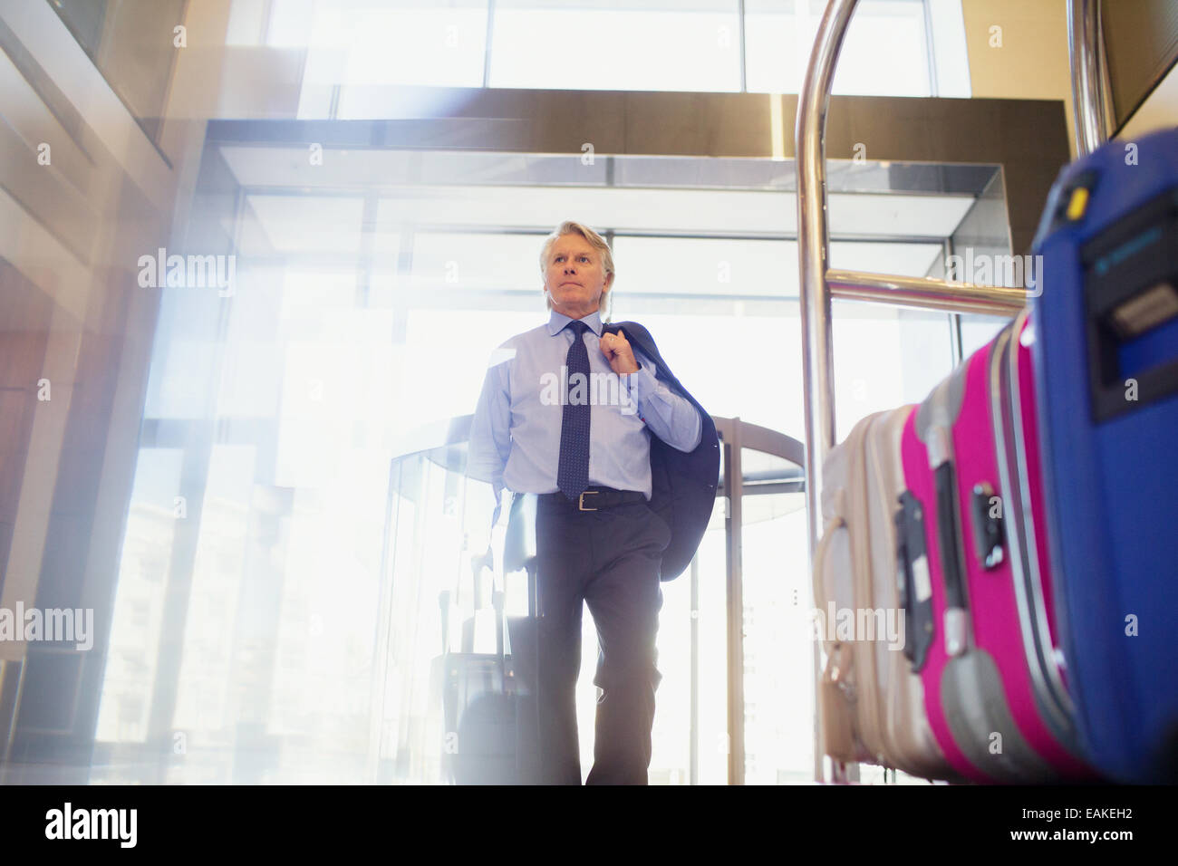 Low angle view of man entering hotel lobby, suitcases on luggage cart in foreground - Stock Image
