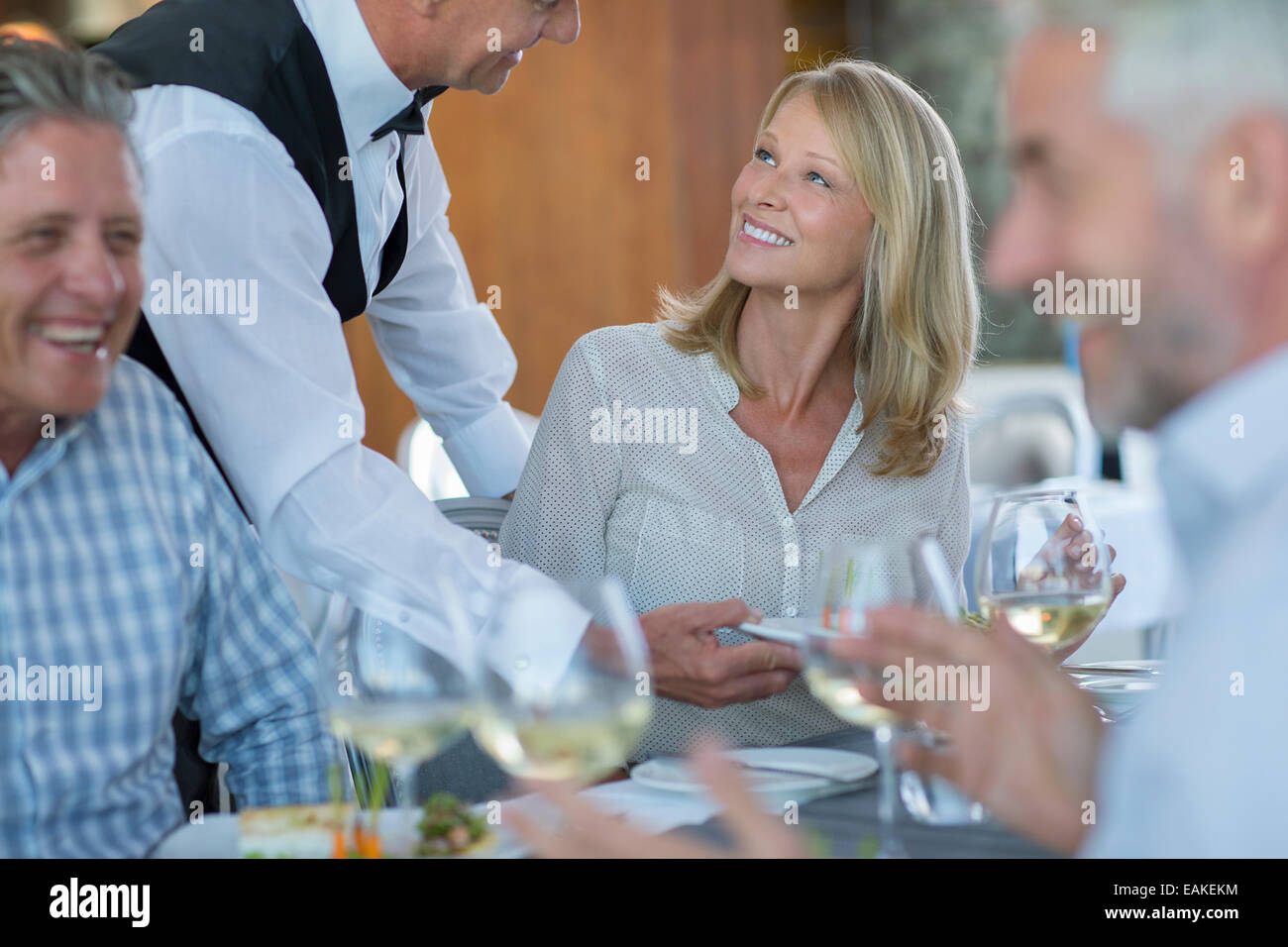 Waiter serving food to woman in restaurant - Stock Image