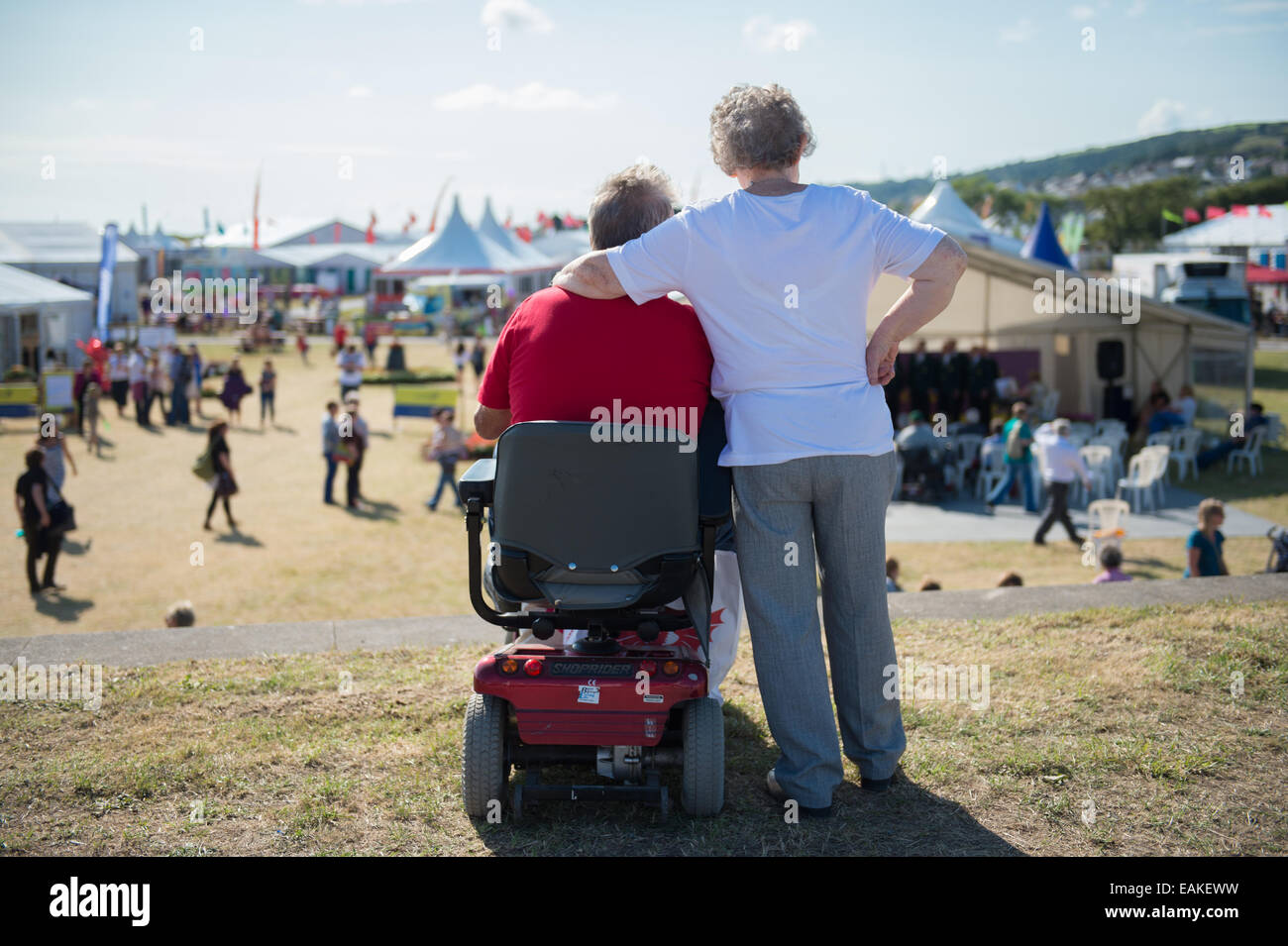 Disability Access:  A disabled, wheelchair-using,  man with his wife at the National Eisteddfod of Wales 2014 - Stock Image