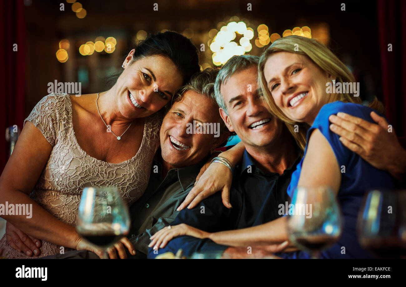 Portrait of smiling mature couples sitting together in restaurant - Stock Image