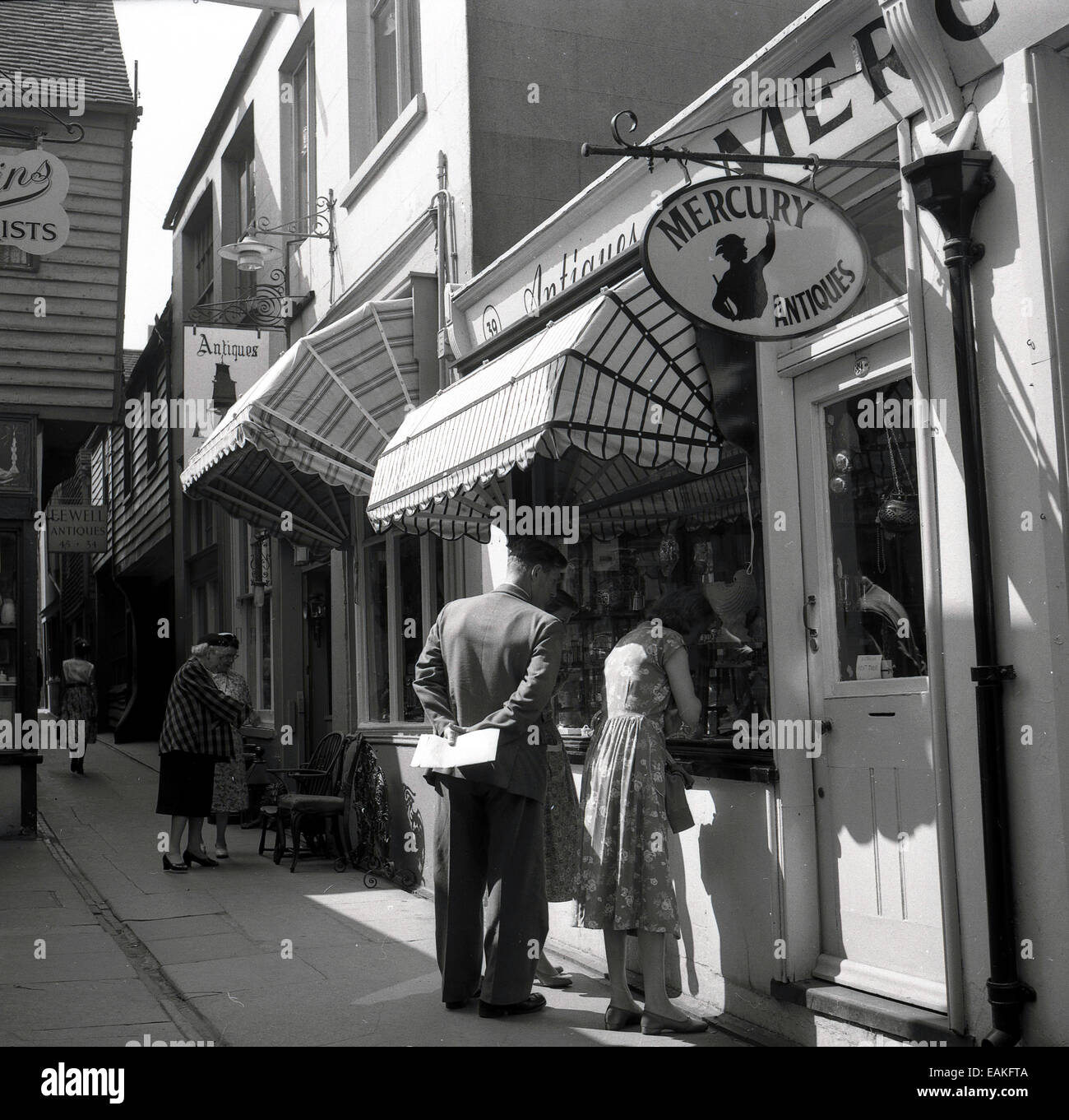 1950s, historical, a couple looking in the window of an antique shop, in an alleyway in the old part of Hastings, - Stock Image