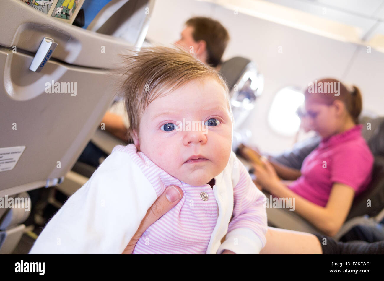 Travelling on an aeroplane with a one month old baby girl - Stock Image
