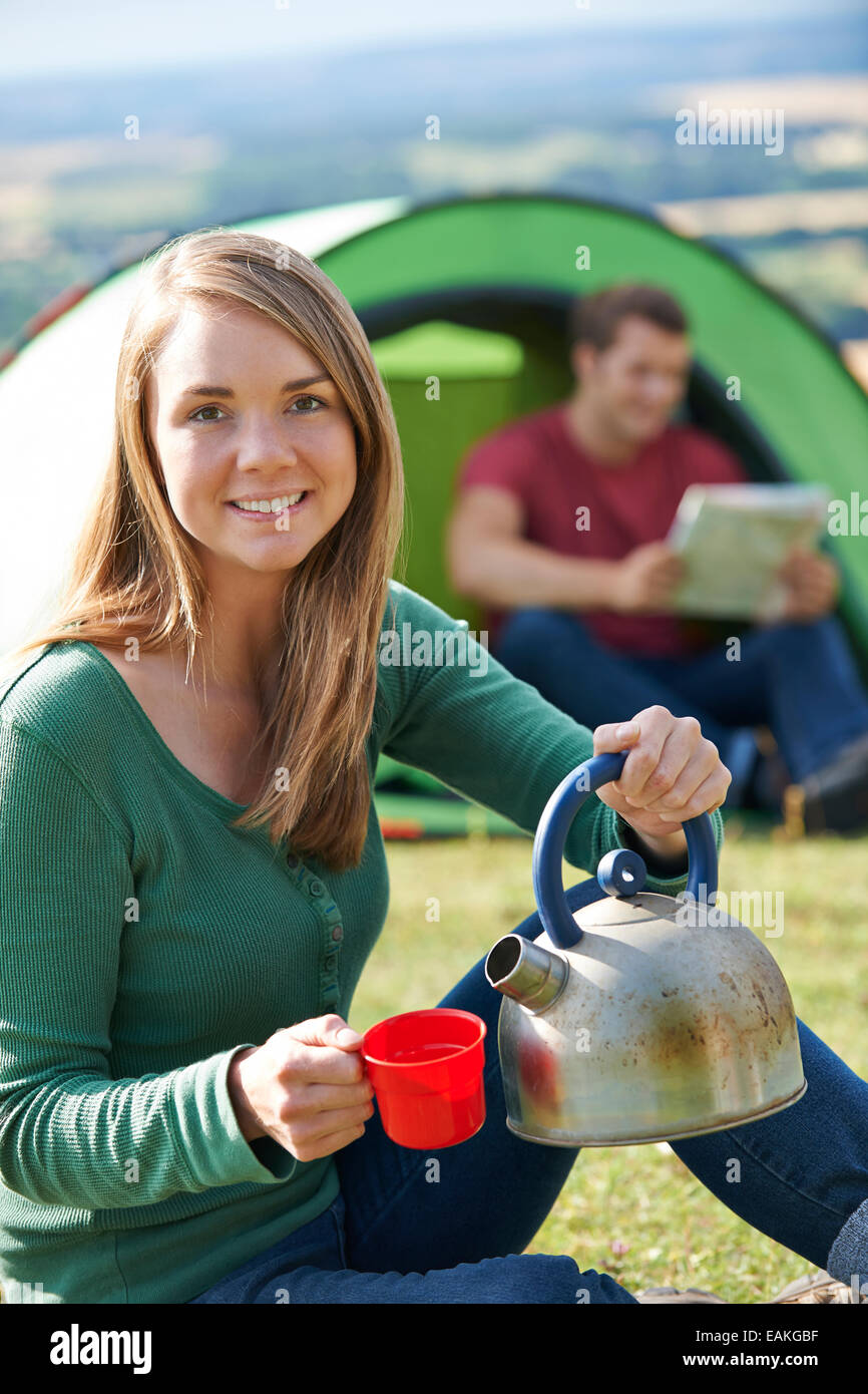 Couple Making Hot Drink Whilst Camping In Countryside - Stock Image
