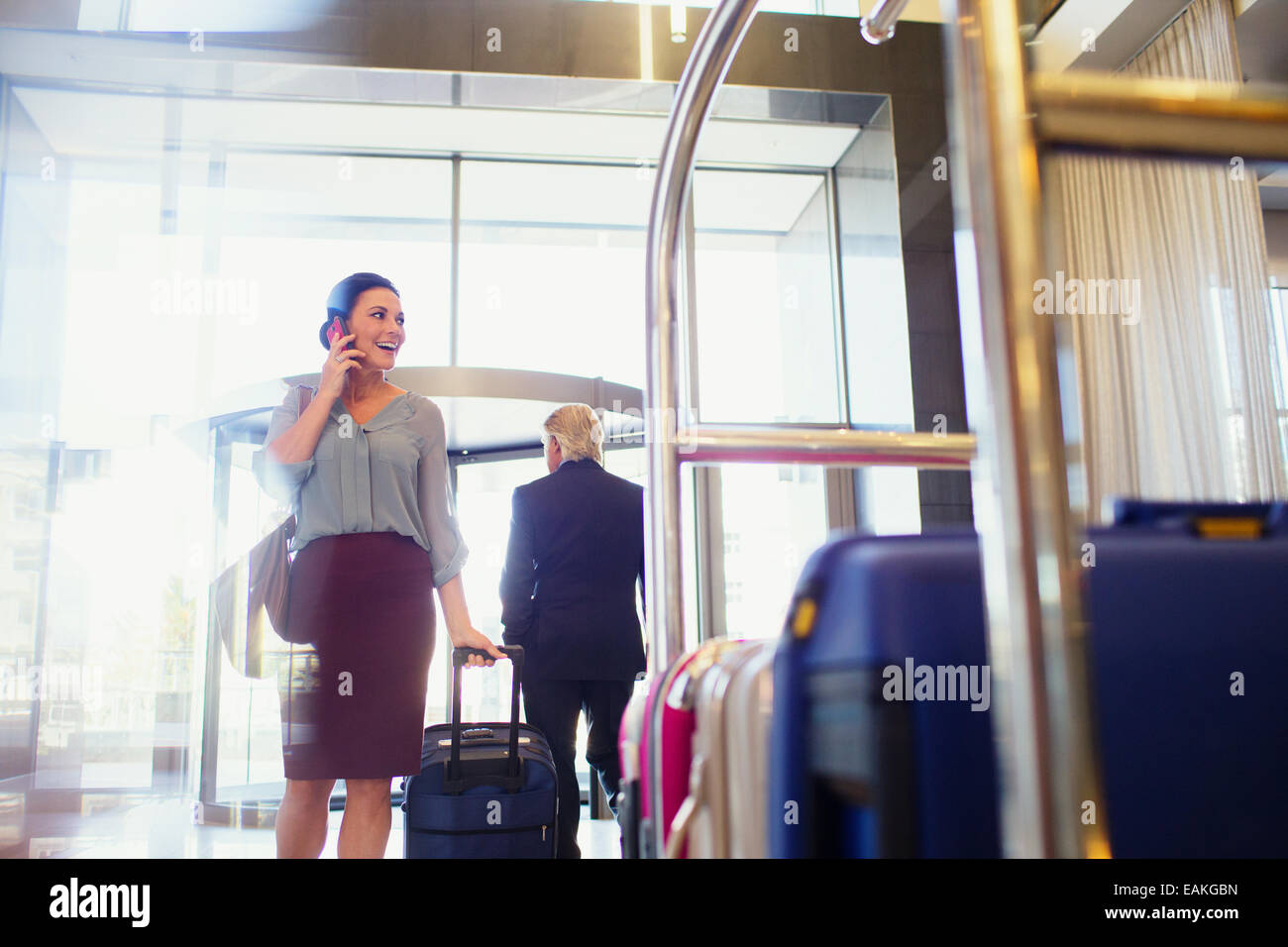 Smiling woman talking on phone in hotel lobby, luggage cart in foreground - Stock Image