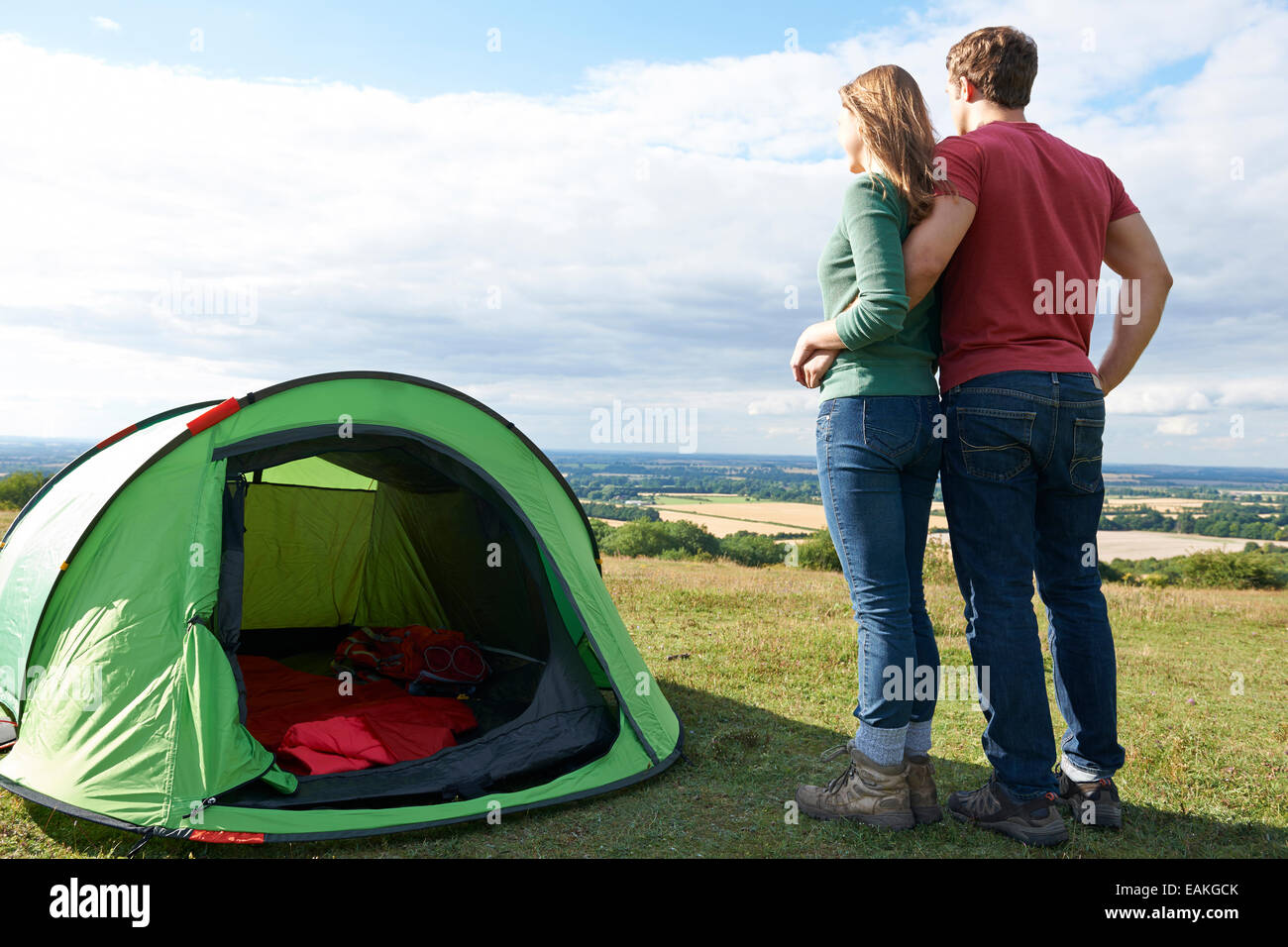Couple Camping In Countryside Standing By Tent - Stock Image