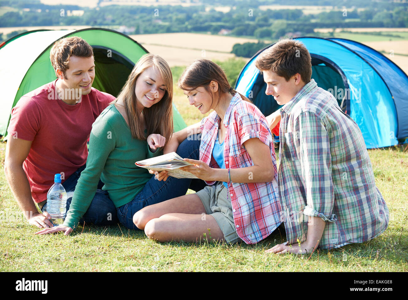 Group Of Young Friends Camping In Countryside Reading Map - Stock Image
