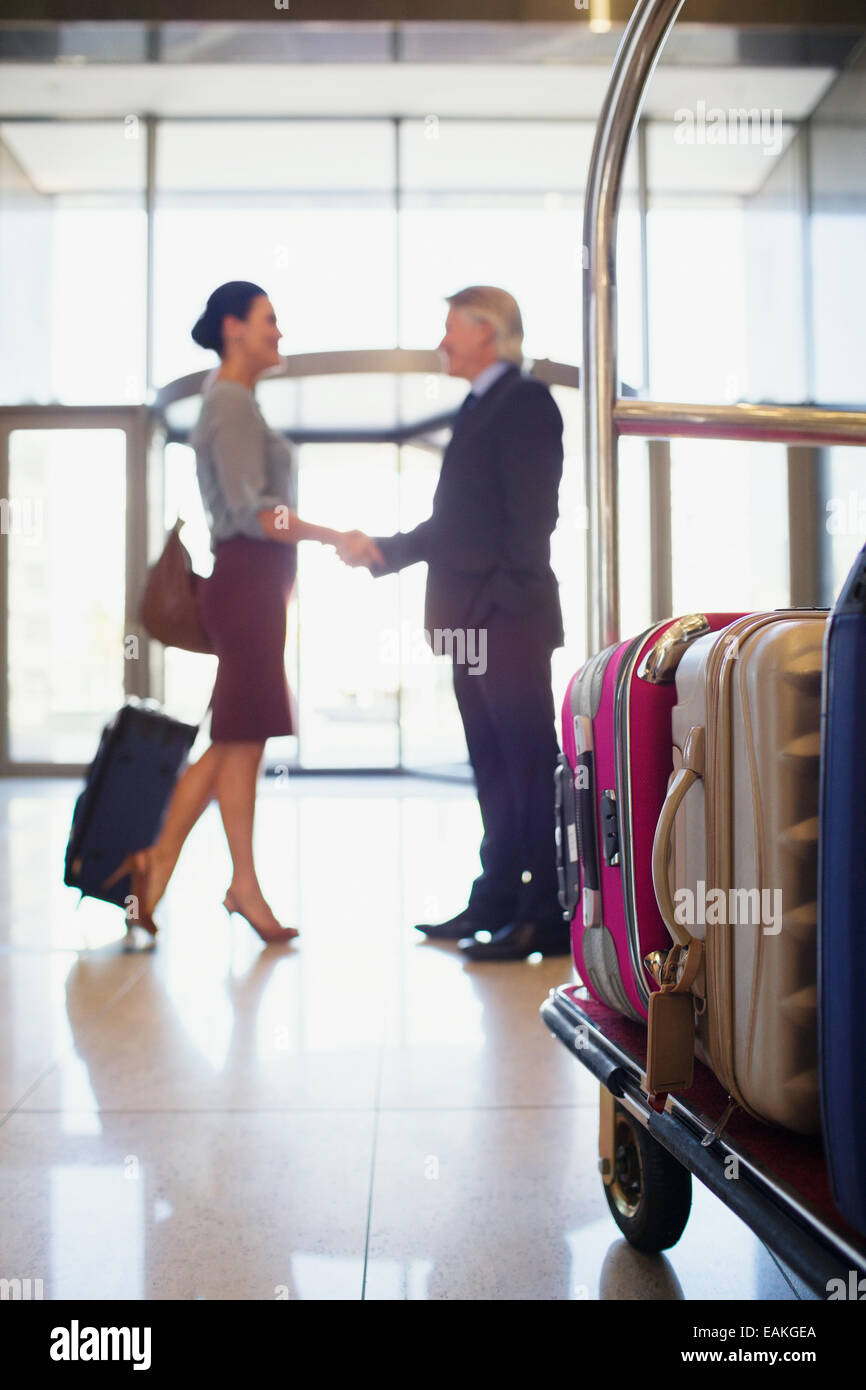 Man and woman shaking hands in hotel lobby, luggage cart in foreground - Stock Image