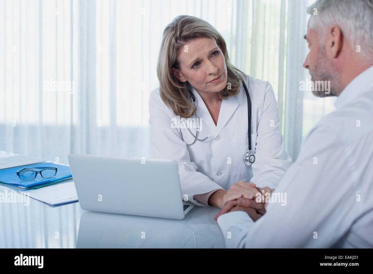 Female doctor sitting at desk with laptop and consoling patient - Stock Image