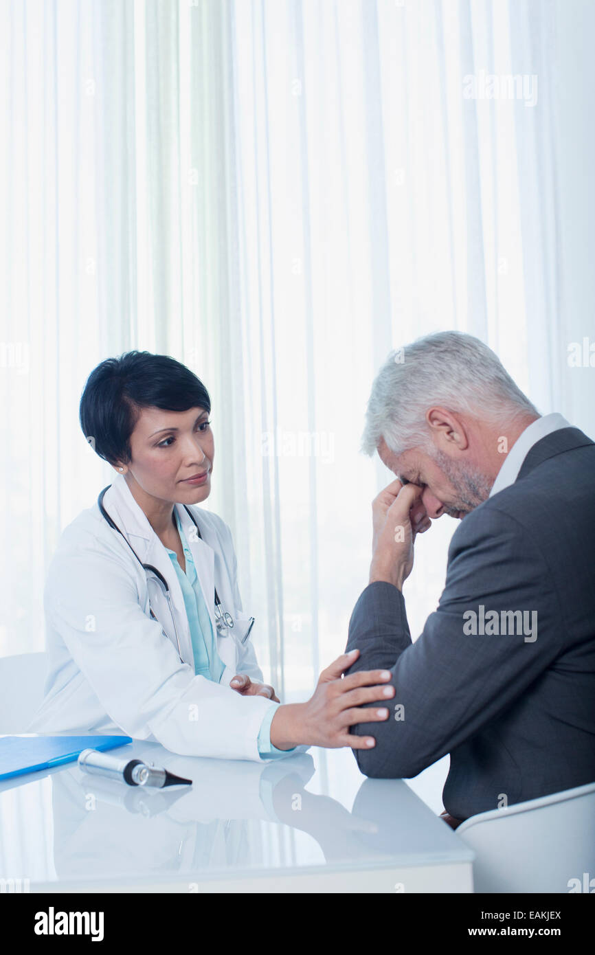 Female doctor sitting at desk and consoling sad patient Stock Photo