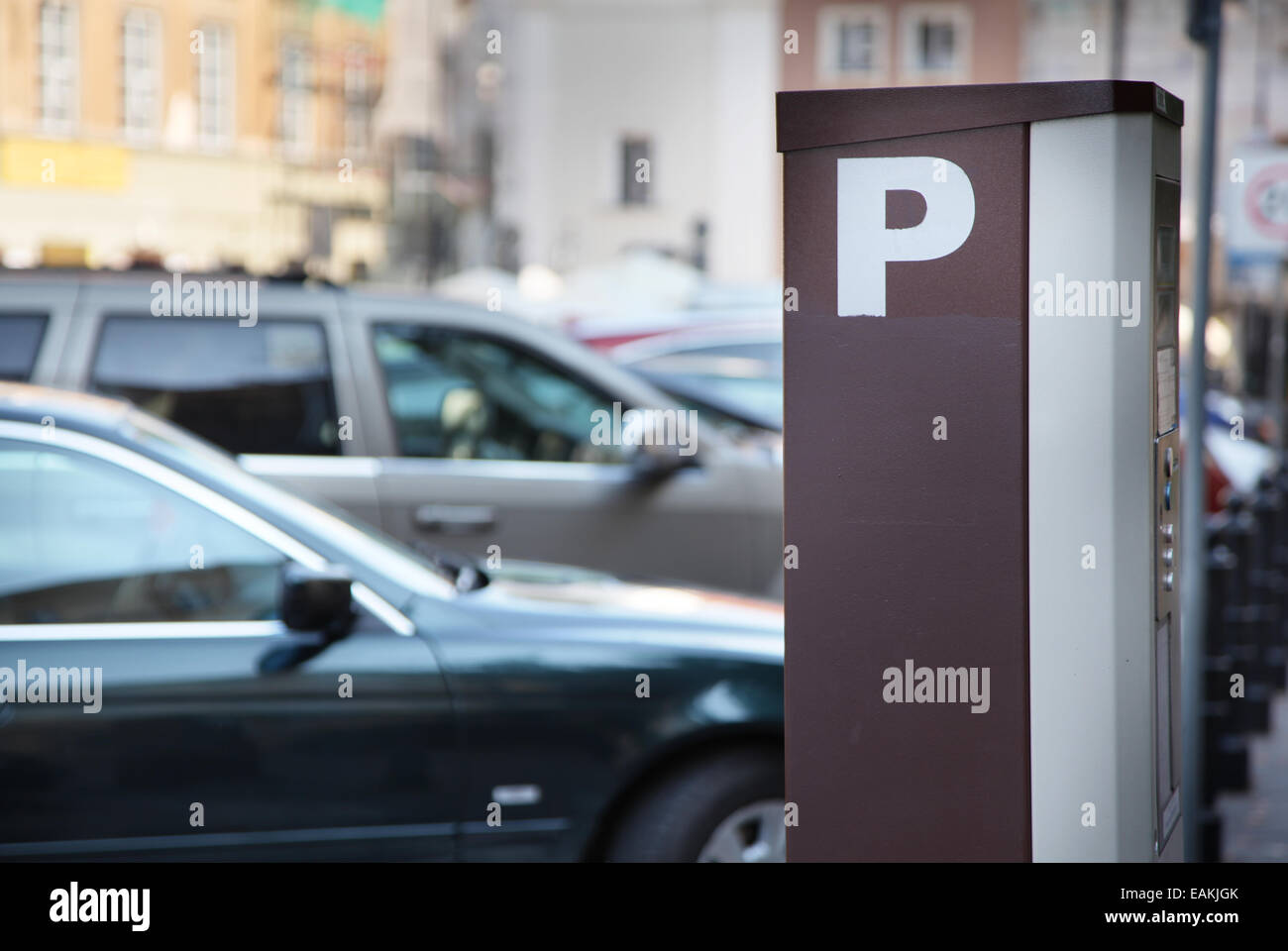 Parking meter in the town. Blurred cars on the background. - Stock Image