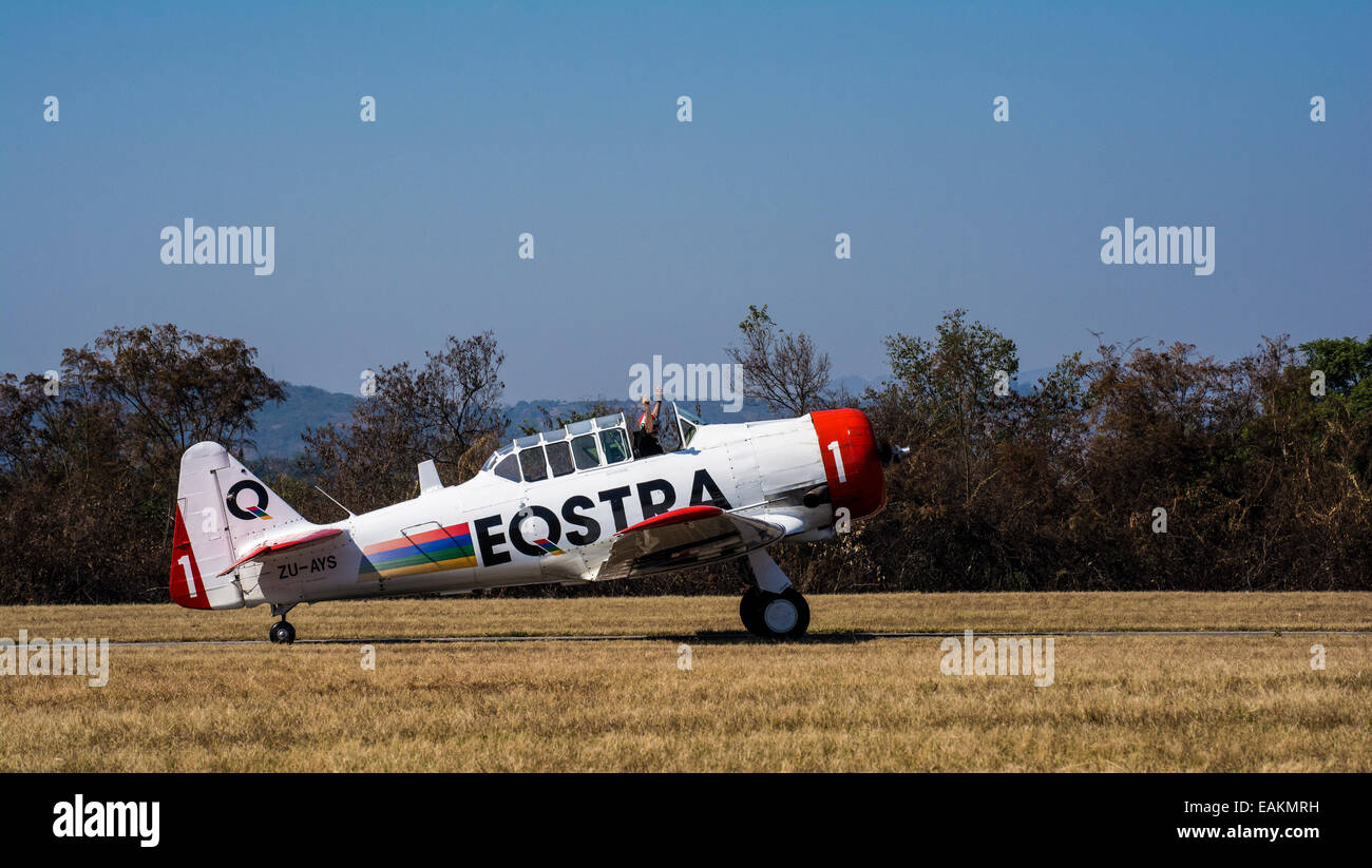 A pilot in a Harvard holding up his arms celebrating a successful demonstration and landing at the Lowveld Air Show - Stock Image