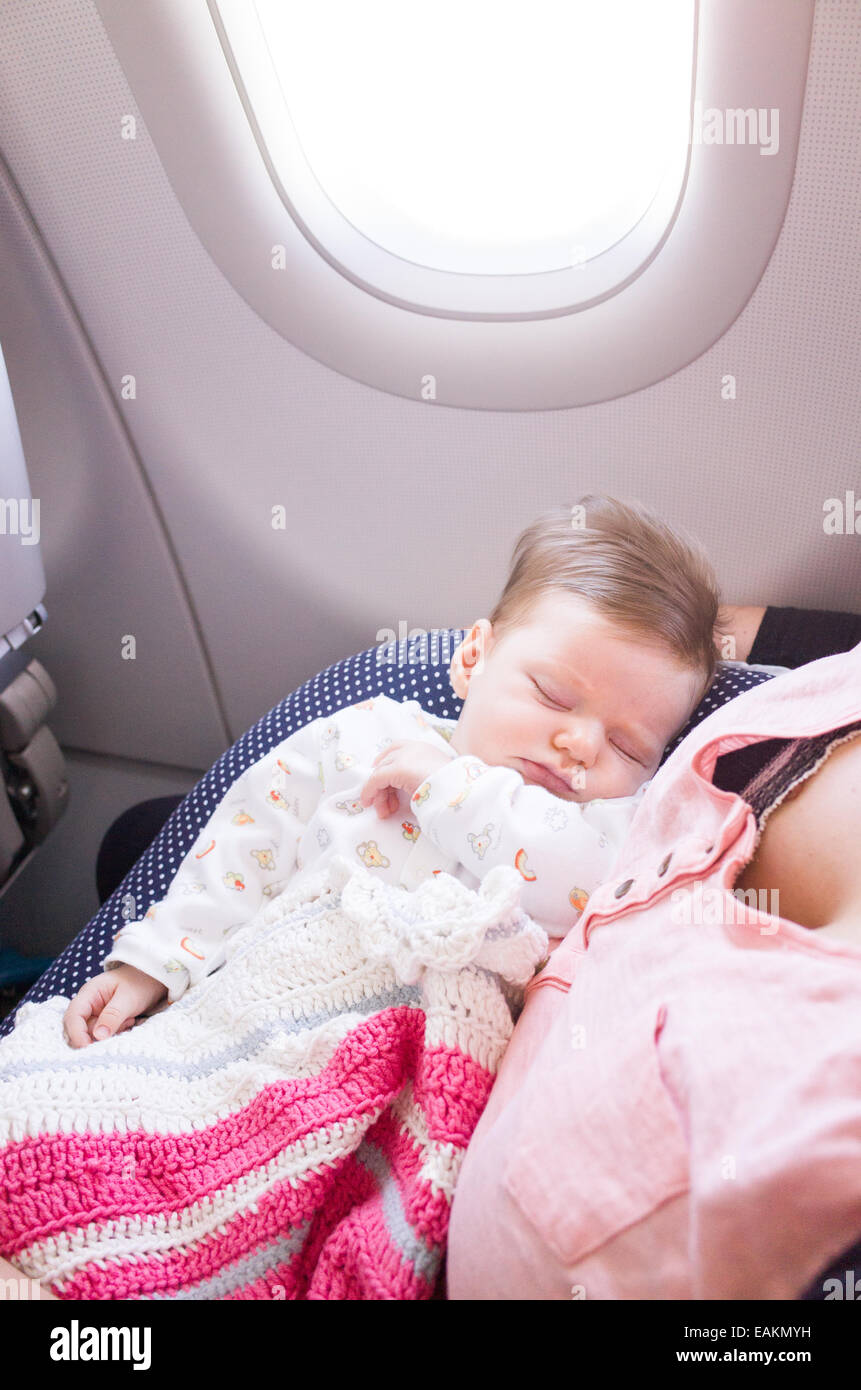 Mother travelling with a two month old baby girl on an aeroplane - Stock Image