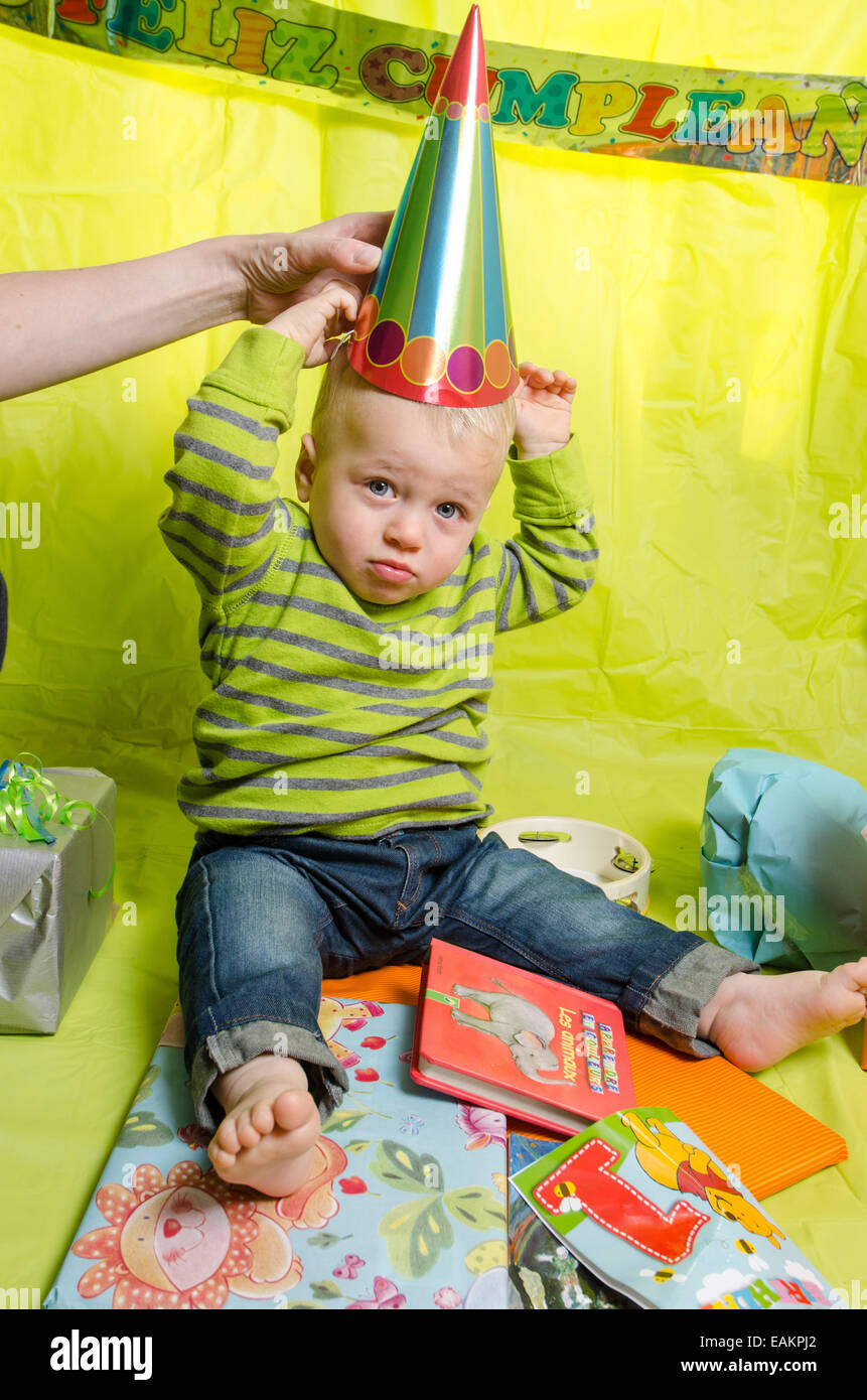 A baby boy (12 months old) is being made to wear a pointy hat. - Stock Image