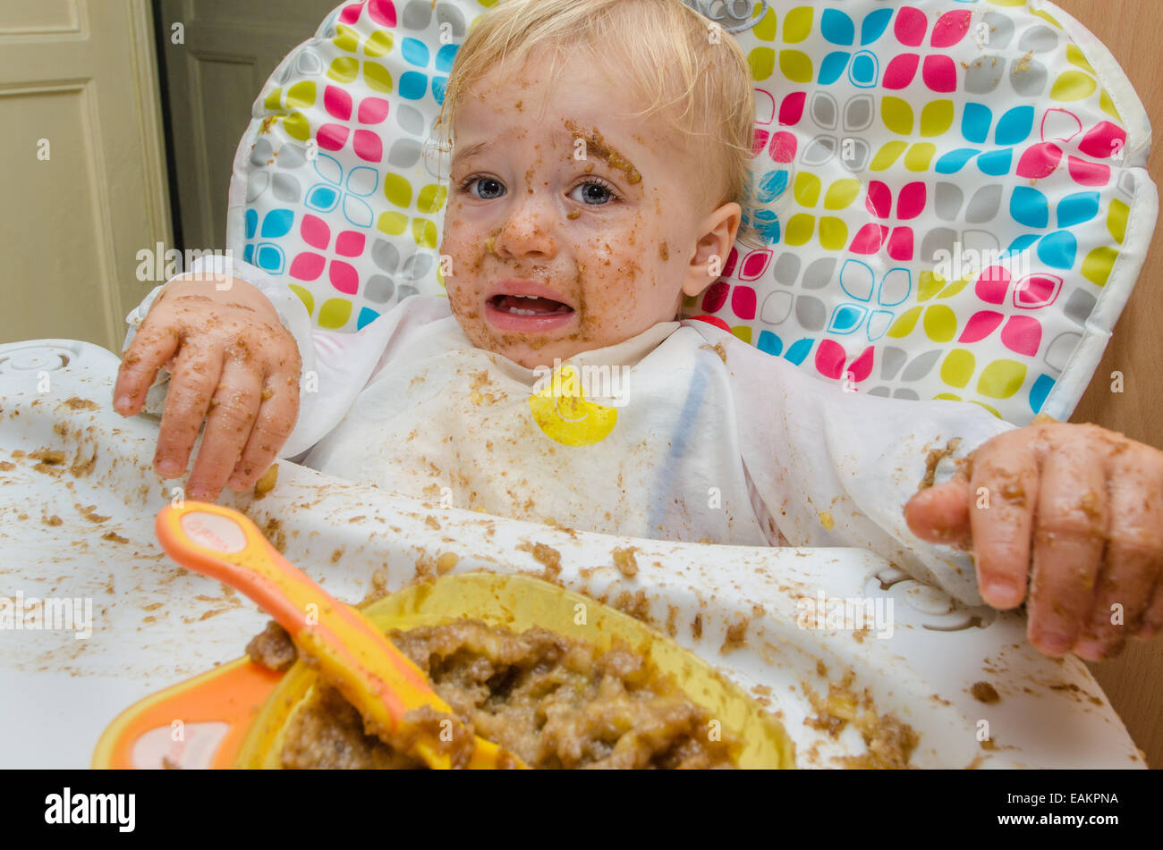 A baby boy (ca. 18 months old) makes a terrible mess of his meal. - Stock Image