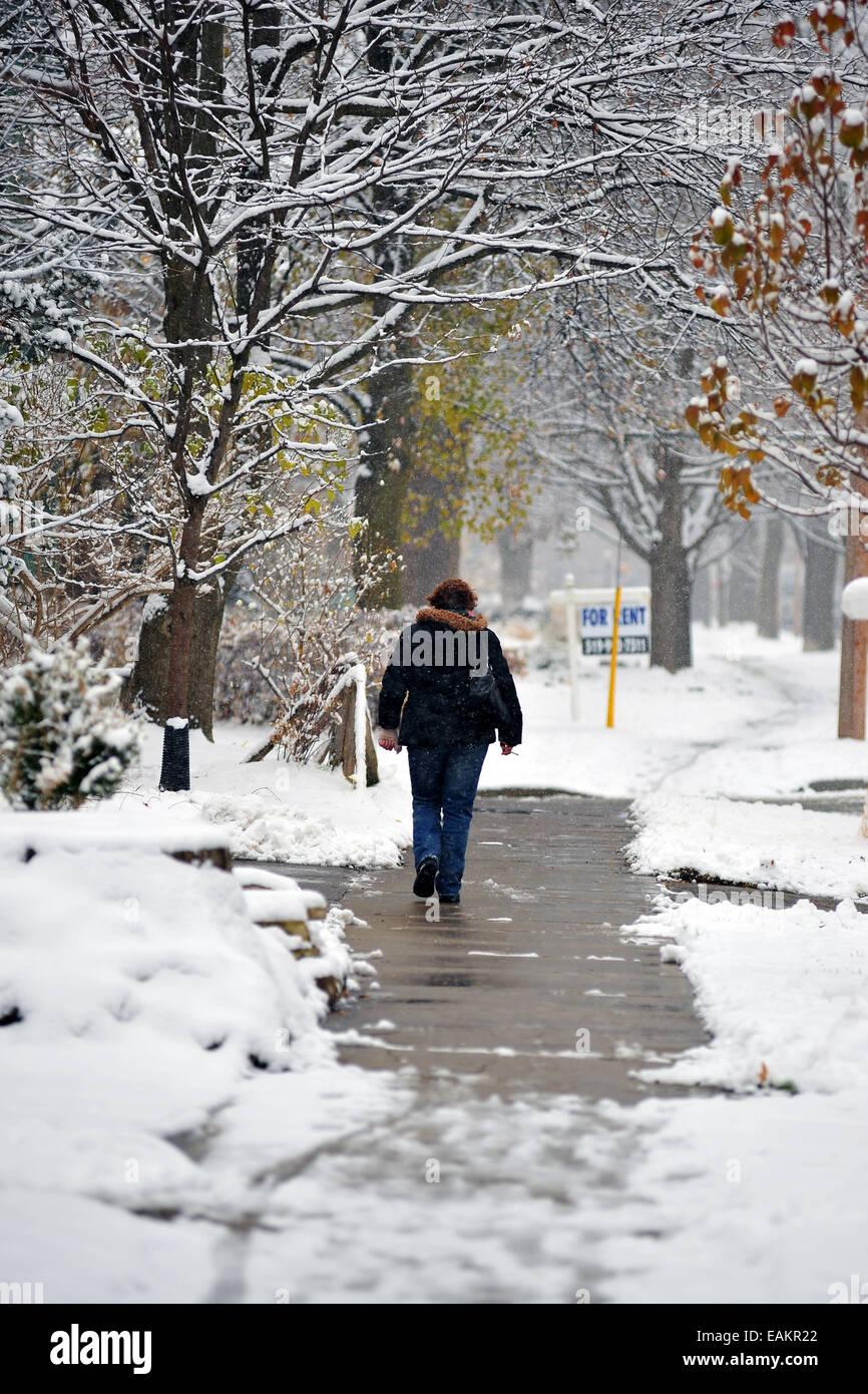 A woman walks down a snowy street in London, Ontario. Stock Photo