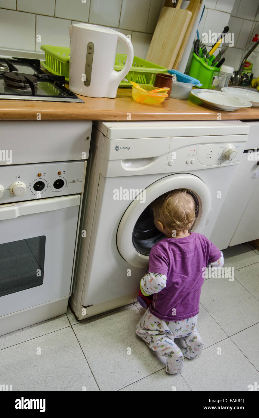 A baby boy (ca. 18 months old) watches laundry being washed in a washing machine. Stock Photo