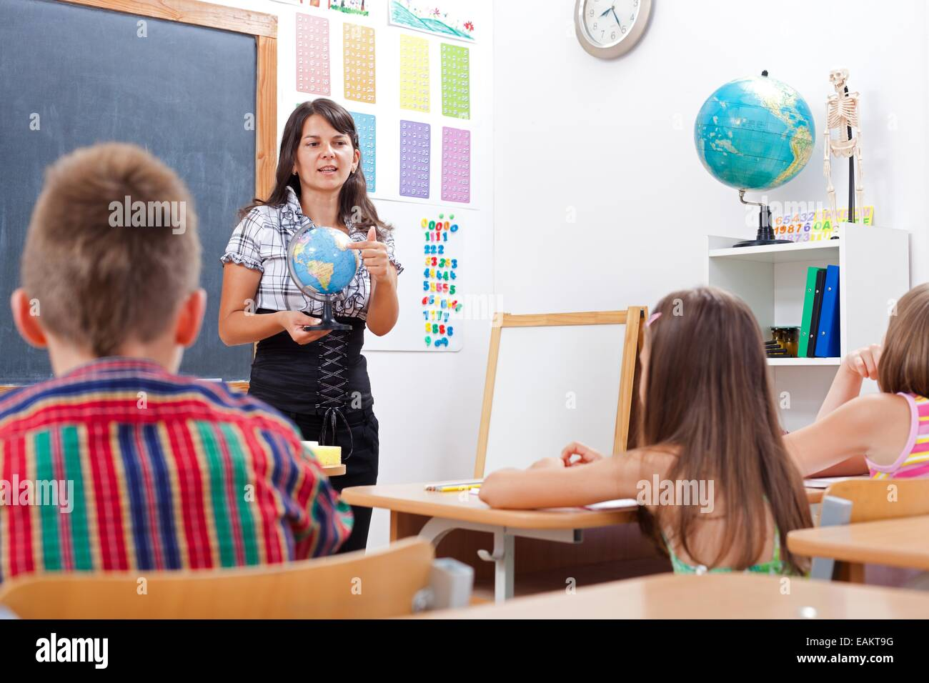 Teacher talking about Earth globe, while children is attending her - Stock Image
