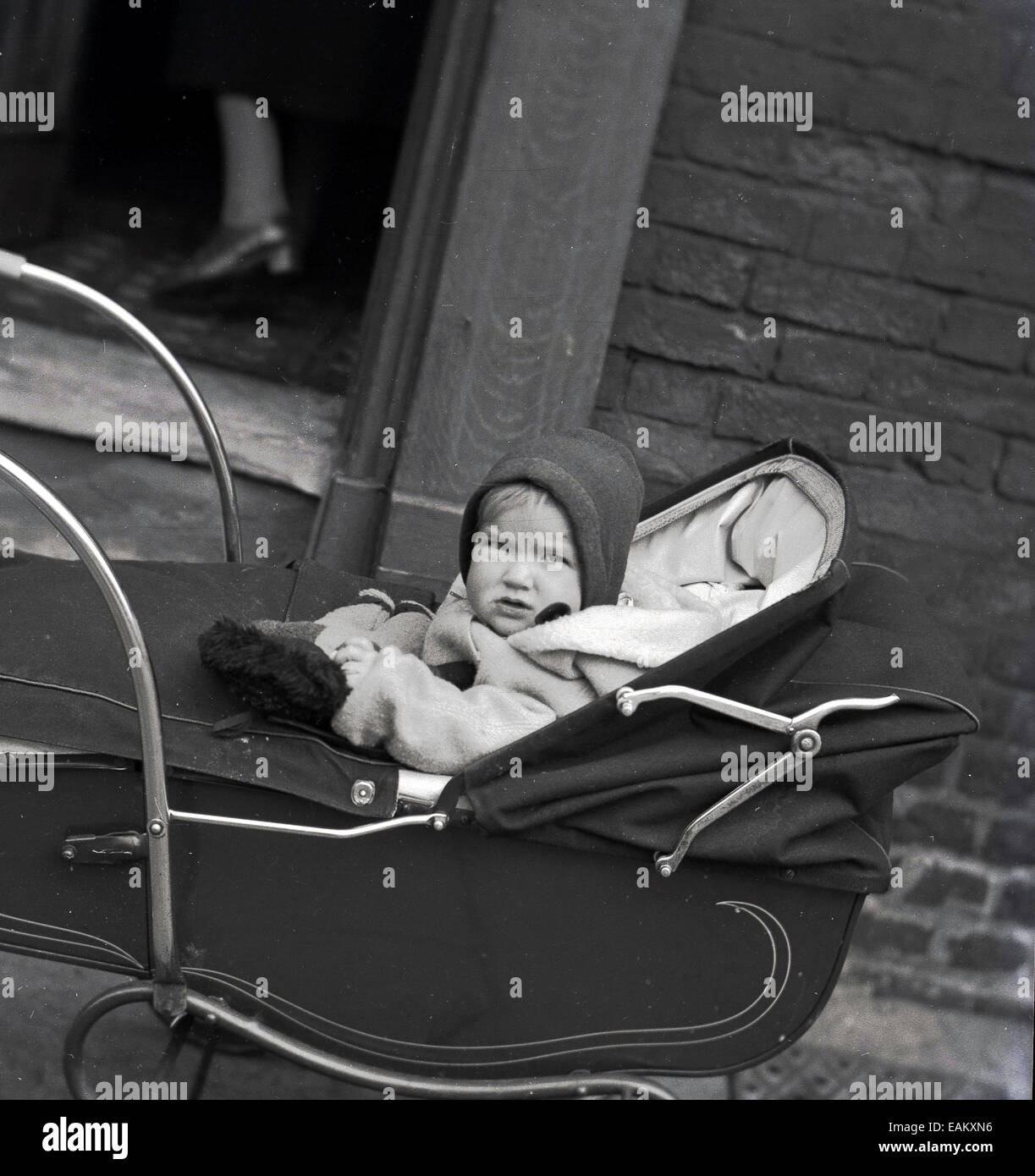 1950s Historical Picture Showing A Young Child Sitting In Their Pram The Street Outside