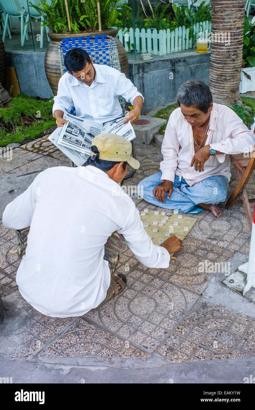Men playing a Vietnamese board game call Xiangqi, like chess or checkers, on the sidewalk in Can Tho, Mekong Delta, - Stock Image