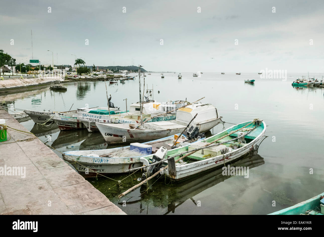 Fishing boats tied up at dock along the Melecon and anchored out on the Bay of Campeche, Campeche, Mexico. - Stock Image