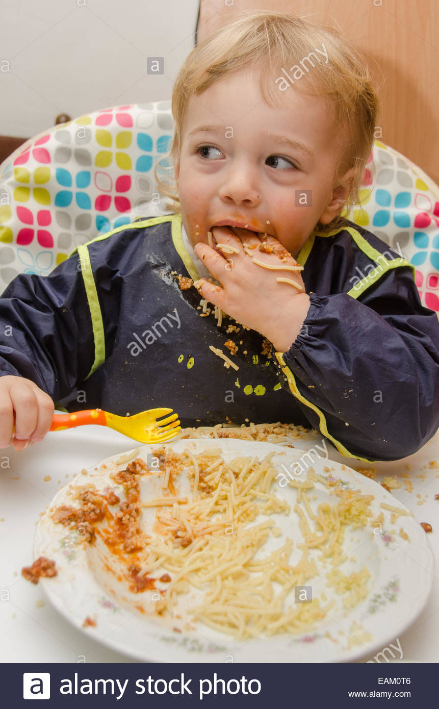A little boy (2 years old) finishes a plate of noodles and tomato sauce - Stock Image
