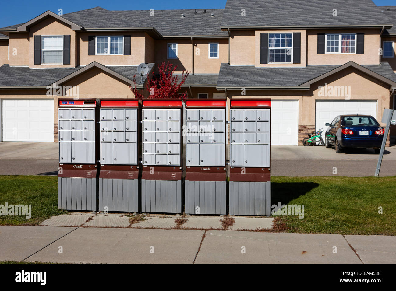 row of canada post mailboxes on sidewalk in suburban neighbourhood saskatoon Saskatchewan Canada Stock Photo