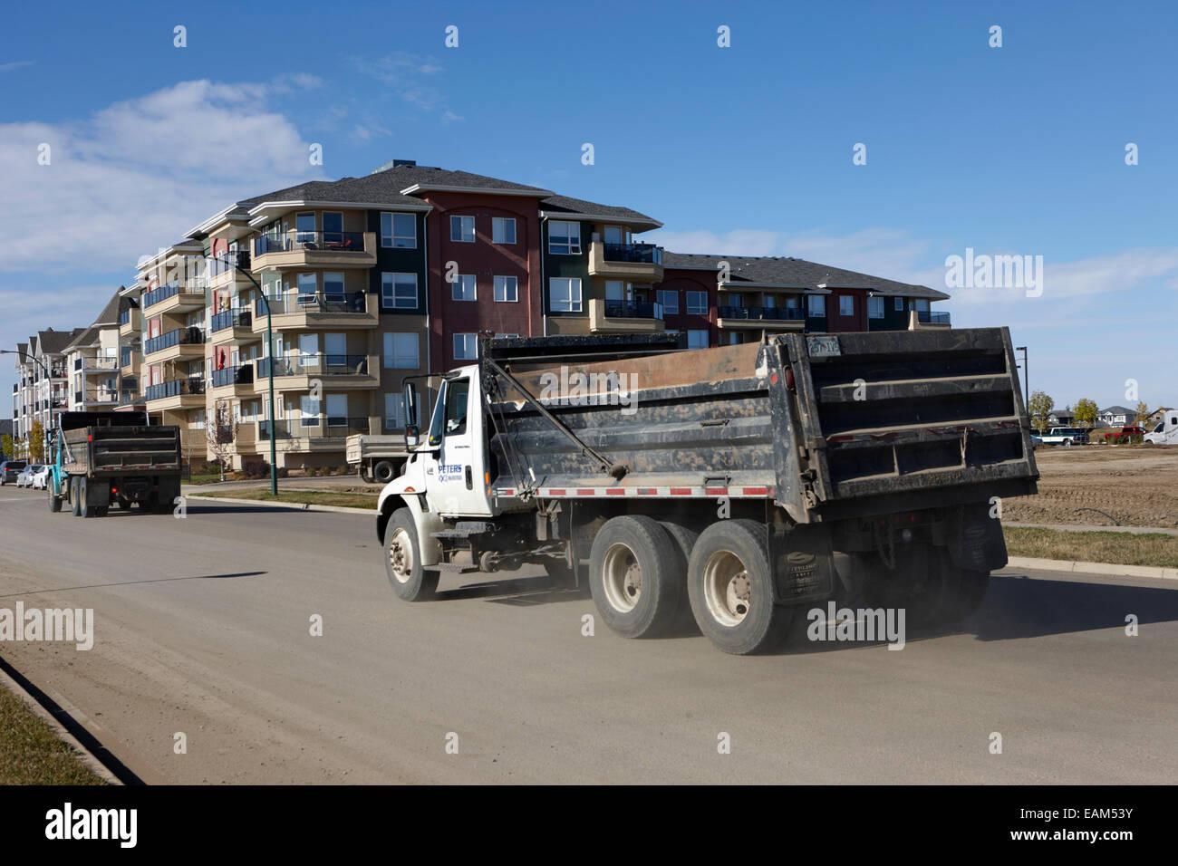 construction dump trucks at new condominium building in suburban neighbourhood saskatoon Saskatchewan Canada - Stock Image