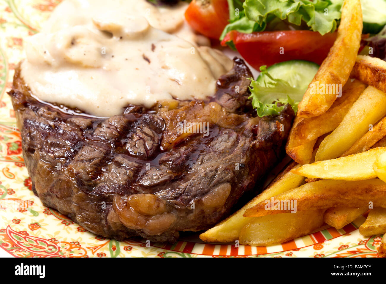 Closeup of grilled rib-eye beef steak served with mushroom sauce, salad and potato chips. - Stock Image
