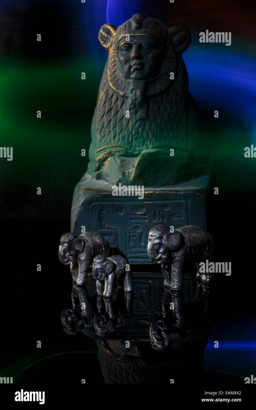 Mystical Sphinx statue with colored lights and elephants in the foreground. Reflection of sphinx and elephants. - Stock Image
